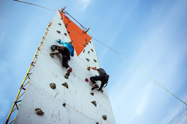 Two young athlete's compete in climbing a vertical climbing wall on the sky background