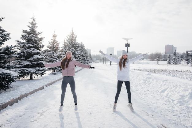 두 젊은 운동 소녀는 화창한 겨울 날 달리기 전에 워밍업을 합니다. 건강한 삶의 방식.