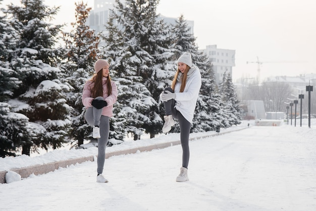 두 명의 젊은 운동 소녀가 맑은 겨울 날에 달리기 전에 워밍업을합니다. 건강한 삶의 방식.