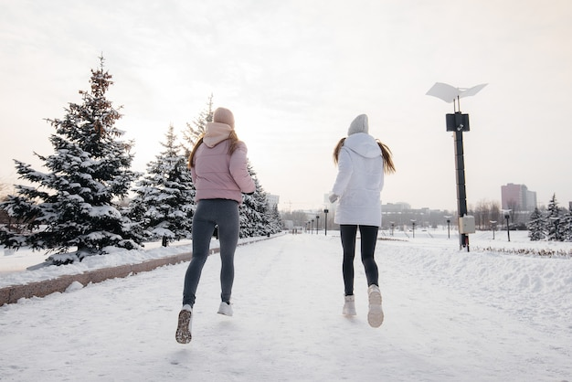 맑은 겨울 날에 공원에서 실행 두 젊은 체육 소녀. 건강한 삶의 방식.