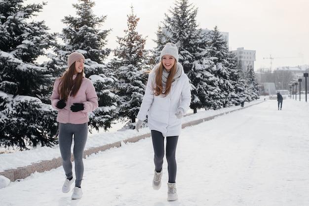 두 젊은 체육 소녀 걷고 맑은 겨울 날에 스포츠를 재생합니다. 건강한 삶의 방식.