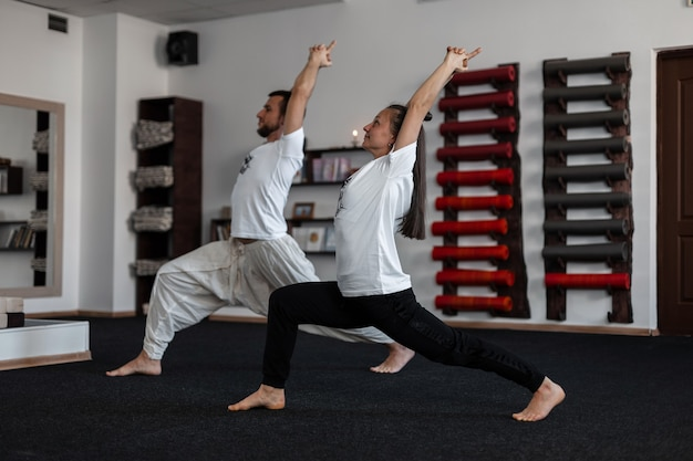Two young athletic people stand in yoga pose and keep their balance. man trainer shows woman a stretching exercise. pair training.