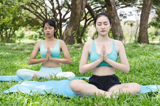 Two young attractive athlete asian woman practicing yoga in the park nature outdoor on green grass in the morning, meditation and healthy relaxation lifestyle
