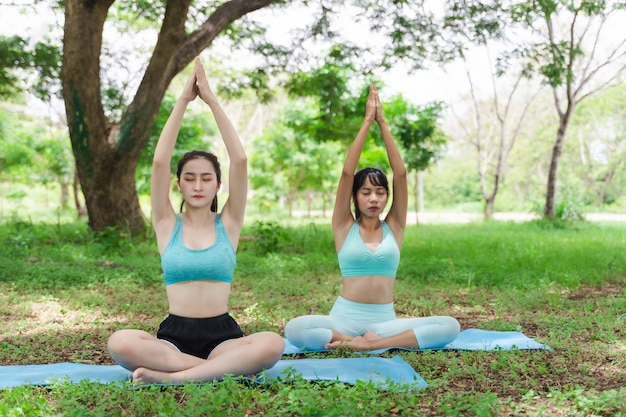 Two young attractive athlete asian woman practicing yoga in the park nature outdoor on green grass in the morning