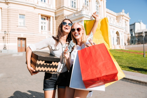 Две молодые привлекательные девушки, стоящие с хозяйственными сумками на улице
