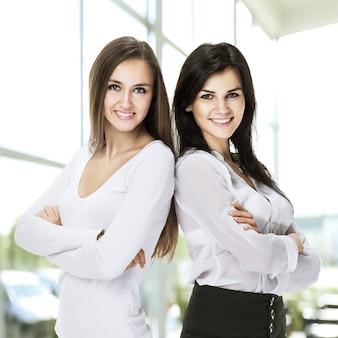 Две молодые, привлекательные успешные деловые женщины, стоящие дядькой, скрестили руки в офисе