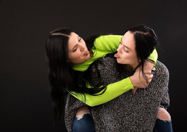 2人の若い魅力的な女性がお互いの舌を孤立させている