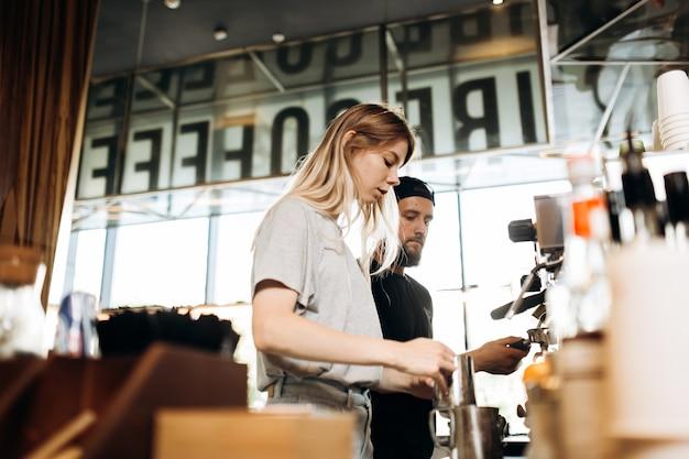 Два молодых бариста, блондинка и стильный мужчина с бородой, вместе готовят кофе в кофеварке в уютной кофейне. .
