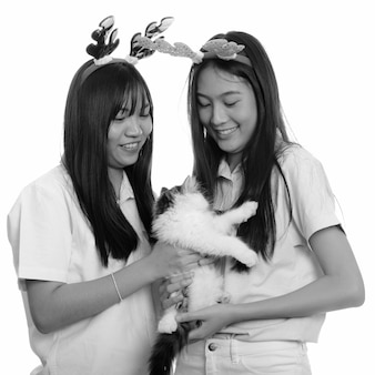 Two young beautiful asian teenage girls together isolated against white wall in black and white