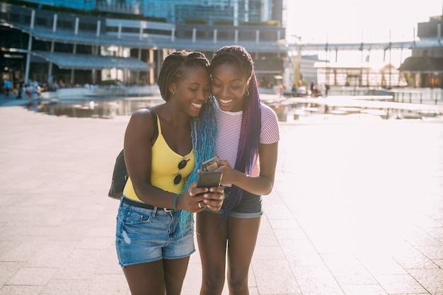 Two young beautiful black sisters outdoor using smartphone