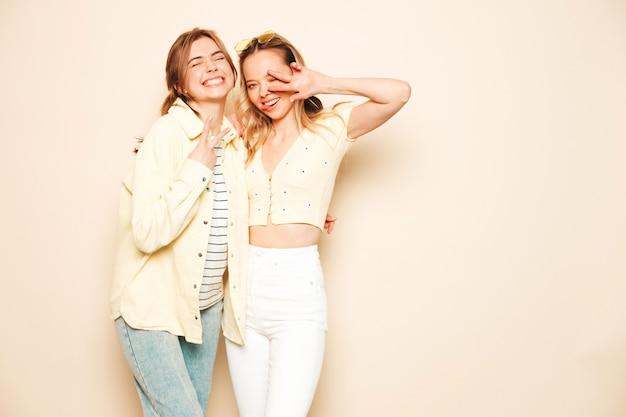 トレンディな夏の服を着た2人の若い美しいブロンドの笑顔の流行に敏感な女性