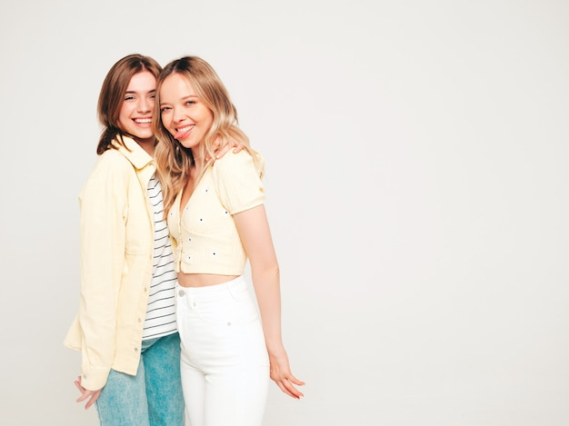 Two young beautiful blond smiling hipster female in trendy summer clothes