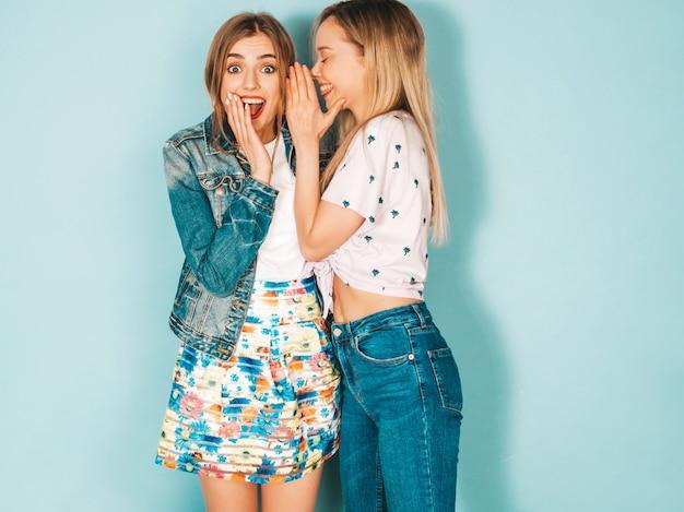 Две молодые красивые белокурые улыбающиеся хипстерские девочки в модной летней повседневной одежде.