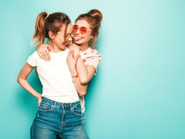 Две молодые красивые белокурые улыбающиеся хипстерские девочки в модных летних хипстерских джинсовых одеждах. сексуальные беззаботные женщины позируют возле синей стены. модные и позитивные модели с удовольствием в солнцезащитных очках