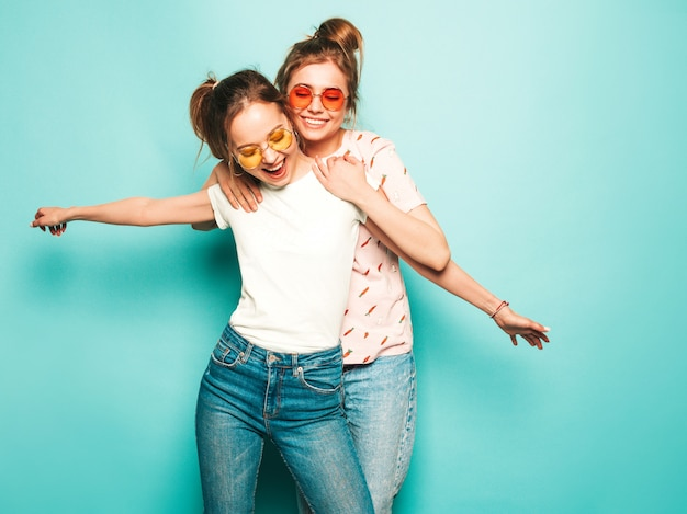 トレンディな夏のヒップスタージーンズの服で2人の若い美しいブロンド笑顔流行に敏感な女の子。水色の壁に近いポーズのセクシーな屈託のない女性。サングラスを楽しんでいるトレンディでポジティブなモデル