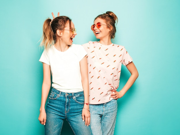 Две молодые красивые белокурые улыбающиеся хипстерские девочки в модных летних хипстерских джинсовых одеждах. сексуальные беззаботные женщины позируют возле синей стены. модные и позитивные модели с удовольствием