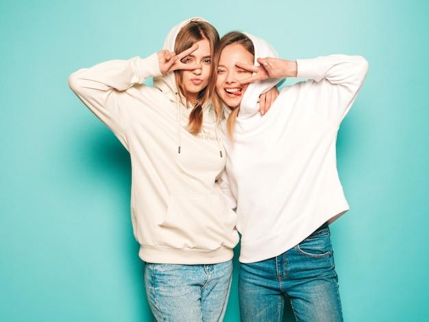 Две молодые красивые белокурые улыбающиеся хипстерские девочки в модной летней толстовке с капюшоном одеваются. сексуальные беззаботные женщины позируют возле синей стены. модные и позитивные модели демонстрируют знак мира в солнцезащитных очках