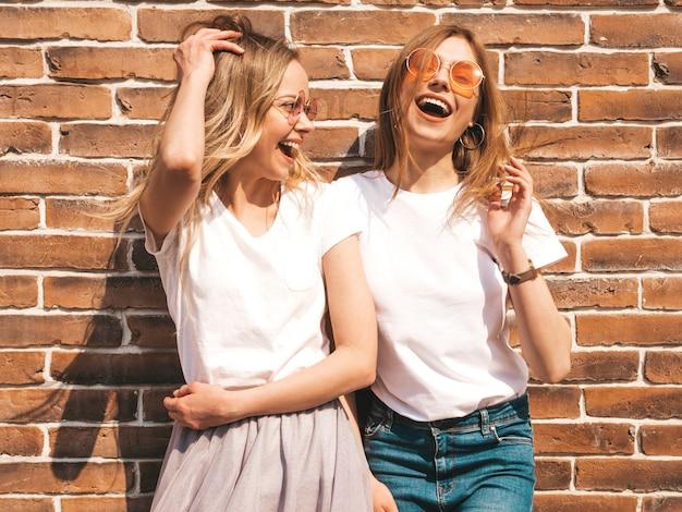 Две молодые красивые белокурые улыбающиеся хипстерские девочки в модной летней белой футболке одеваются. , позитивные модели веселятся в солнечных очках