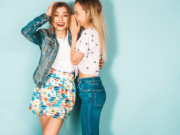 Two young beautiful blond smiling hipster girls in trendy summer casual clothes.