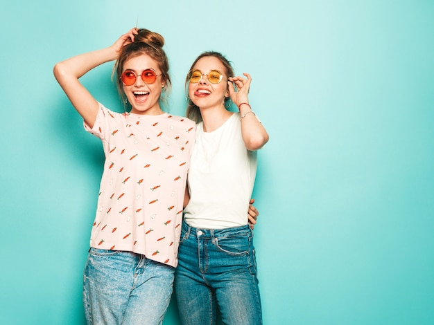 Two young beautiful blond smiling hipster girls in trendy summer hipster jeans clothes. sexy carefree women posing near blue wall. trendy and positive models having fun in sunglasses