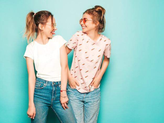 Due giovani belle ragazze sorridenti bionde dei pantaloni a vita bassa in vestiti d'avanguardia dei jeans dei pantaloni a vita bassa dell'estate. donne spensierate sexy che posano vicino alla parete blu. modelli trendy e positivi che si divertono con gli occhiali da sole