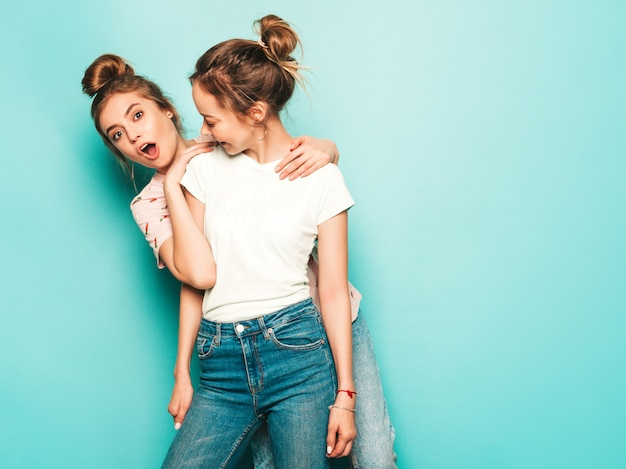 Two young beautiful blond smiling hipster girls in trendy summer hipster jeans clothes. sexy carefree women posing near blue wall. trendy and positive models having fun