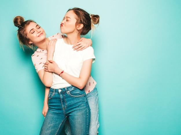Due giovani belle ragazze sorridenti bionde dei pantaloni a vita bassa in vestiti d'avanguardia dei jeans dei pantaloni a vita bassa dell'estate. donne spensierate sexy che posano vicino alla parete blu. modelli alla moda e positivi che si divertono