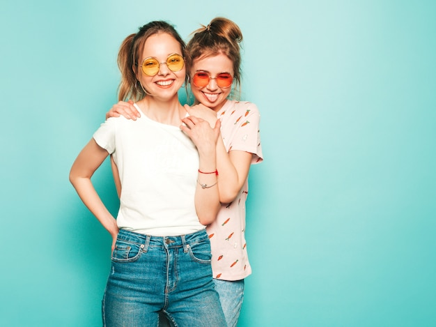 Two young beautiful blond smiling hipster girls in trendy summer hipster jeans clothes. sexy carefree women posing near blue wall. trendy and positive models having fun.