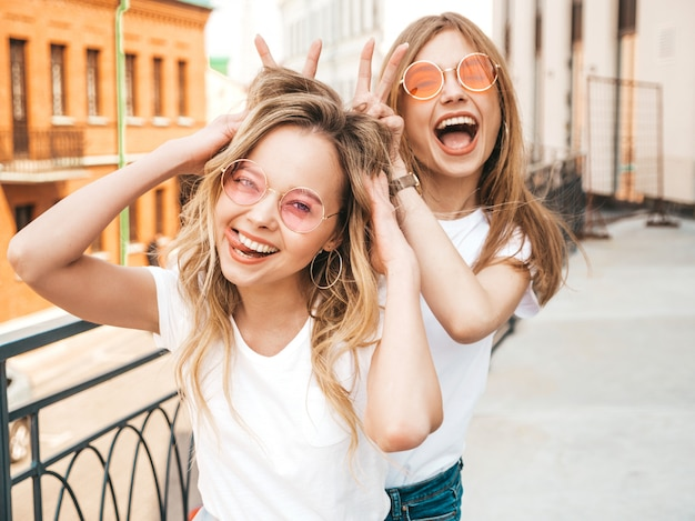Two young beautiful blond smiling hipster girls in trendy summer white clothes.   .positive models having fun in sunglasses.using fingers as bunny ears