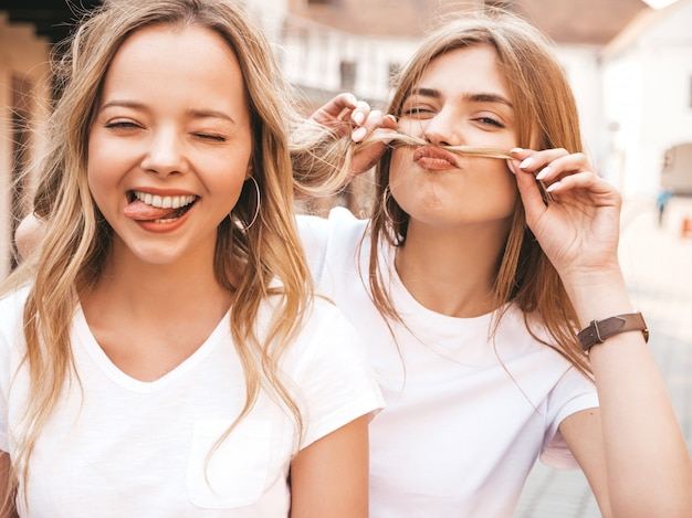 Two young beautiful blond smiling hipster girls in trendy summer white t-shirt clothes. . positive models having fun.making mustache with hair and showing tongue