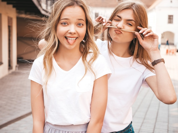 Two young beautiful blond smiling hipster girls in trendy summer white t-shirt clothes. positive models having fun.making mustache with hair and showing tongue