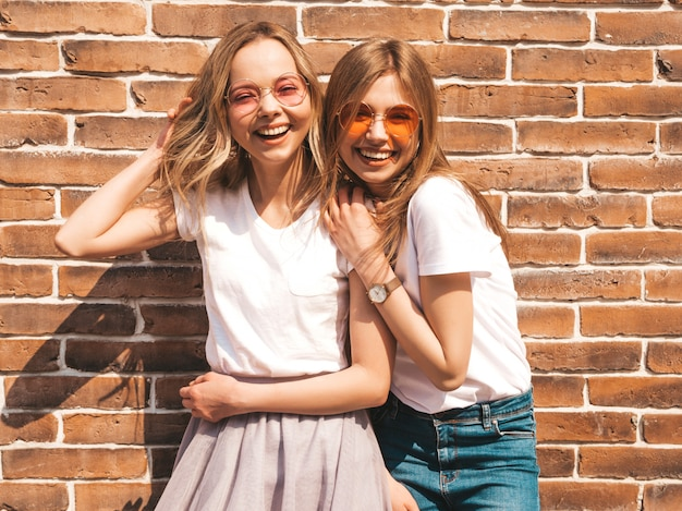 Two young beautiful blond smiling hipster girls in trendy summer white t-shirt clothes.  . positive models having fun in sunglasses