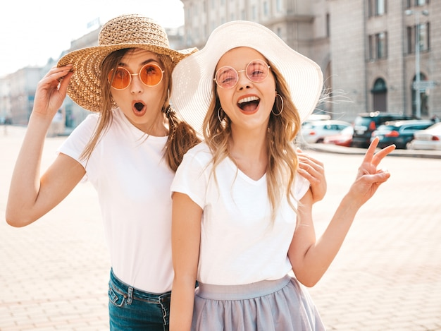 Two young beautiful blond smiling hipster girls in trendy summer white t-shirt clothes. sexy shocked women posing in  the street. surprised models having fun in sunglasses and hat.shows peace sign