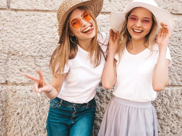 Two young beautiful blond smiling hipster girls in trendy summer white t-shirt clothes. women posing in the street near wall. . showing peace sign
