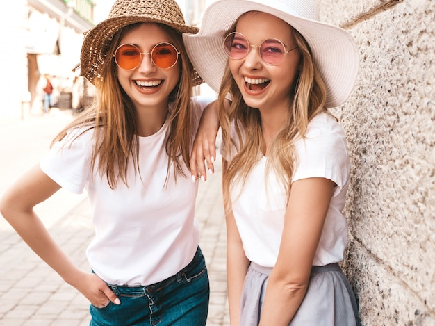 Two young beautiful blond smiling hipster girls in trendy summer white t-shirt clothes. women posing in the street near wall.