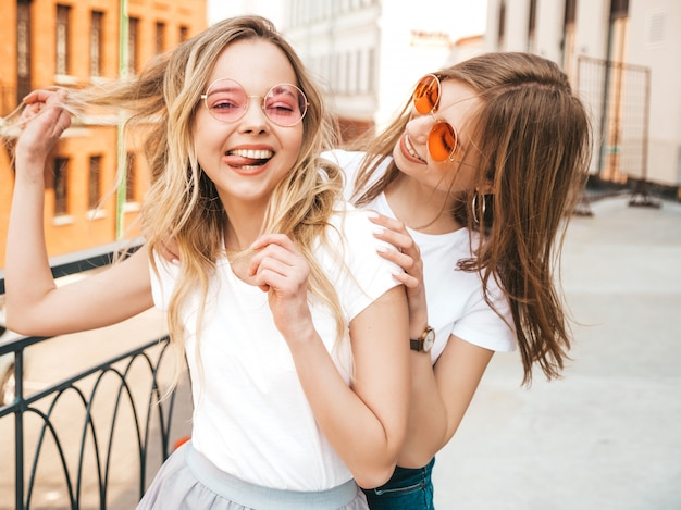 Two young beautiful blond smiling hipster girls in trendy summer white t-shirt clothes. women posing on street . positive models having fun in sunglasses.shows peace sign
