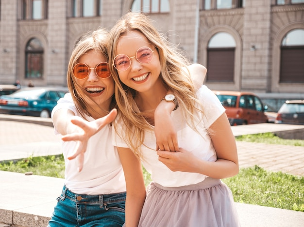 Two young beautiful blond smiling hipster girls in trendy summer white t-shirt clothes.