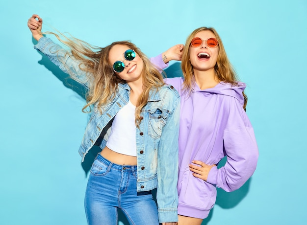Two young beautiful blond smiling hipster women in trendy summer clothes. sexy carefree women posing near blue wall in sunglasses. positive models going crazy