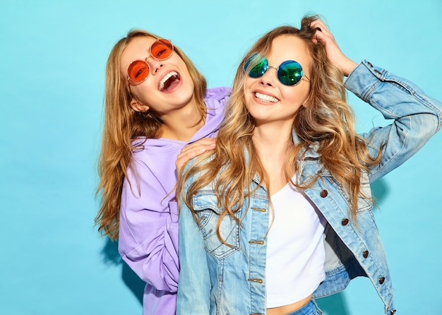Two young beautiful blond smiling hipster women in trendy summer clothes. sexy carefree women posing near blue wall in sunglasses. positive models