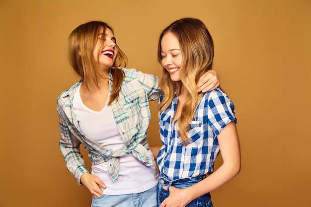 Two young beautiful blond smiling in trendy summer checkered shirts