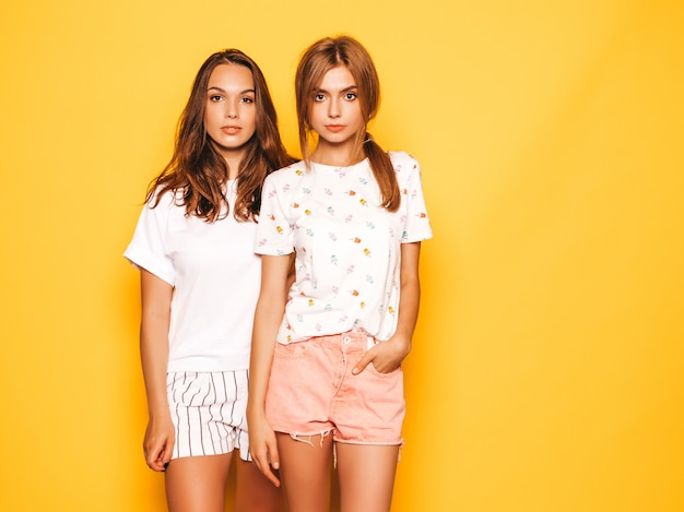Two young beautiful boring hipster girls in trendy summer clothes. sexy carefree women posing near yellow wall