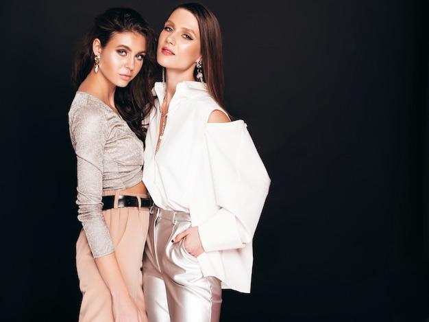 素敵なトレンディな夏の服を着た2人の美しいブルネット少女。セクシーな屈託のない女性がスタジオで黒の上ポーズ