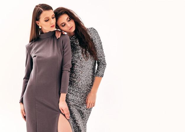 素敵なトレンディな夏の光沢のあるドレスの2人の若い美しいブルネットの女の子