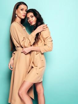 좋은 유행 여름 비슷한 정장에 두 젊은 아름 다운 갈색 머리 여자 옷. 스튜디오에서 파란색 벽 근처 포즈 섹시 평온한 여성