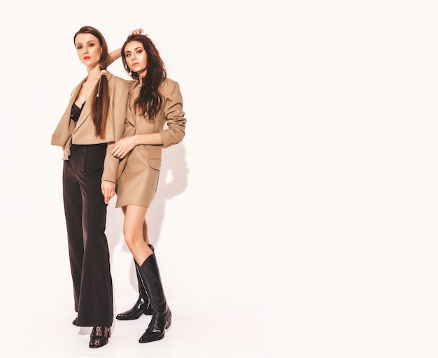 Two young beautiful brunette girls in nice trendy summer similar suits clothes