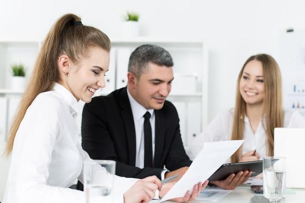 彼らの同僚と相談する2人の若い美しいビジネス女性。ドキュメントとアイデアについて話し合うパートナー