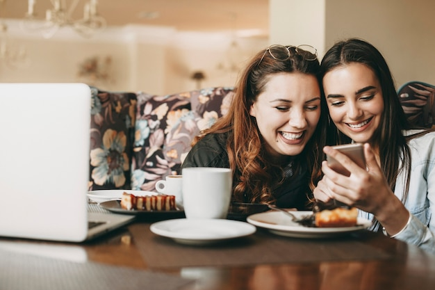 Two young beautiful caucasian woman having fun laughing while looking at a smartphone sitting in a coffee shop.