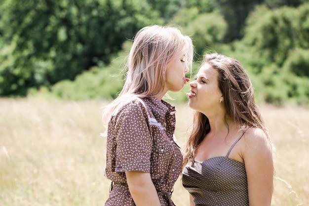 공원에서 초원에 두 젊은 아름 다운 쾌활 한 여자