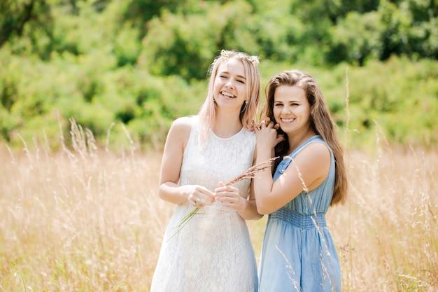 2人の若い美しい陽気な女の子がフィールドを歩きます
