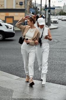 거리에서 포즈를 취하는 두 젊은 아름 다운 유행 소녀. 세련된 선글라스와 밝은 색상의 옷을 입은 모델. 도시 생활입니다. 여성 패션과 친구 개념입니다.